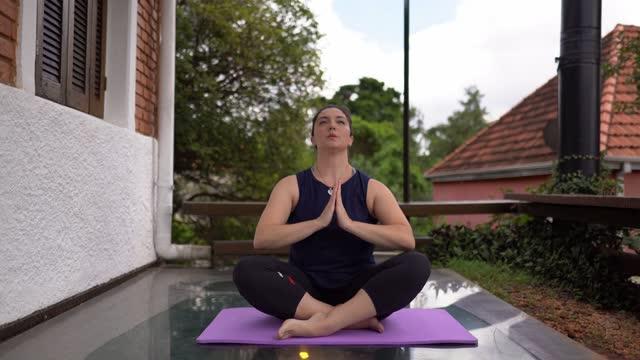 vidéos et rushes de femme méditant en faisant du yoga à la maison - assis en tailleur