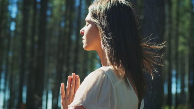vídeos de stock, filmes e b-roll de mulher meditating na floresta - defendendo