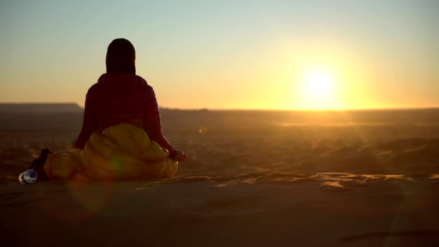 Woman meditating in front of desert sunset