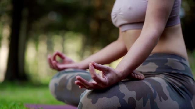 stockvideo's en b-roll-footage met vrouw die in aard mediteert - in kleermakerszit