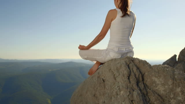 hd: woman meditating in the nature - lotus position stock videos & royalty-free footage