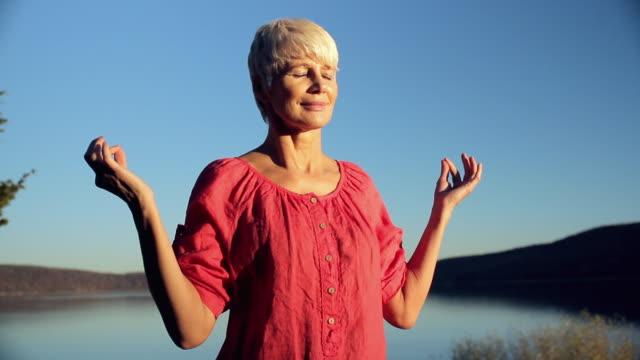 vídeos de stock, filmes e b-roll de cu woman meditating near lakeside / clinton, new jersey, usa - usa