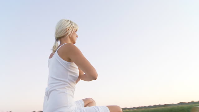 hd slow motion: woman meditating on a hay bale - lotus position stock videos and b-roll footage
