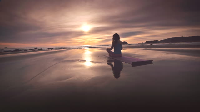 ws pov zo woman meditating on beach / bandon, or, united states  - schneidersitz stock-videos und b-roll-filmmaterial