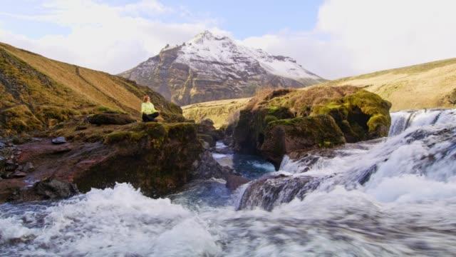 vídeos de stock e filmes b-roll de ms woman meditating on rock overlooking mountain waterfall,iceland - só uma mulher de idade mediana