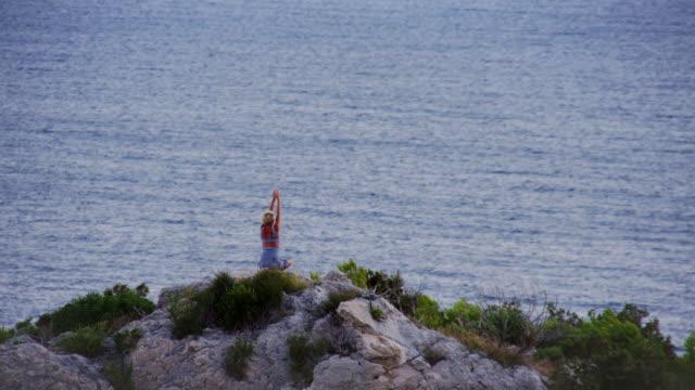 ls donna meditare sulla scogliera - braccio umano video stock e b–roll