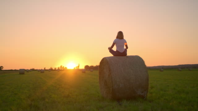 ms woman meditating on top of hay bale in idyllic,rural field at sunset - mindfulness stock videos & royalty-free footage