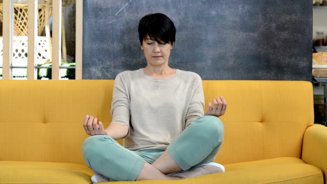 woman meditating on yellow couch - lotus position stock videos & royalty-free footage