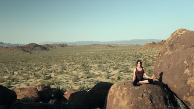 ws pan woman meditating over boulder / palm springs, california, usa - solo una donna di età media video stock e b–roll