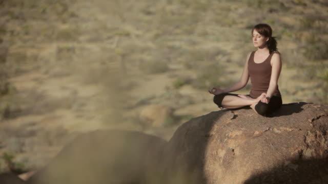vidéos et rushes de ws pan woman meditating over boulder / palm springs, california, usa - assis en tailleur