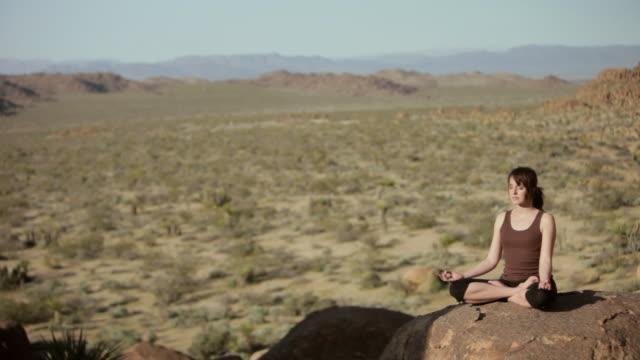 WS PAN Woman meditating over boulder / Palm Springs, California, USA