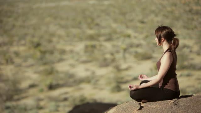 ws pan woman meditating over boulder / palm springs, california, usa - lotusställning bildbanksvideor och videomaterial från bakom kulisserna