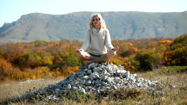 Woman meditating sitting on a stone pyramid in the mountains