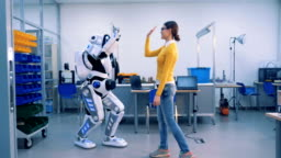 A woman meets a robot in a room. Robot and woman give each other a high-five, then a droid copies her movements with fingers.