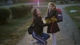 A woman meets her little daughter from school. A girl in a school uniform with a backpack hugs and kisses her mom. Slow motion