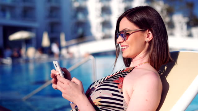 woman messaging with friends on her smartphone - sunbed stock videos & royalty-free footage