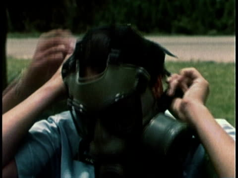 1968 MONTAGE Woman military officer helping man put on gas mask / United States