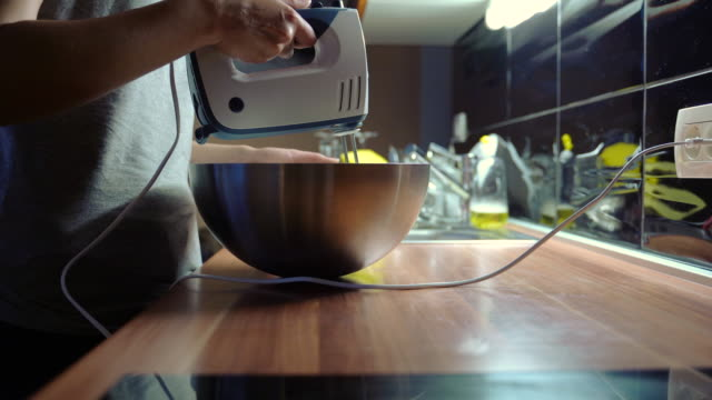 woman mixing ingredients with electric mixer in mixing bowl - mixing bowl stock videos and b-roll footage