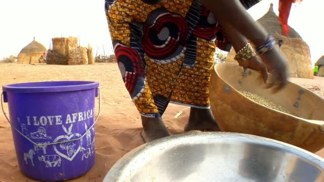 cu, woman mixing millet grain in bowl, low section, niamey, niger - ニジェール点の映像素材/bロール