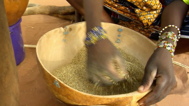 CU, Woman mixing millet grain in bowl, mid section, Niamey, Niger