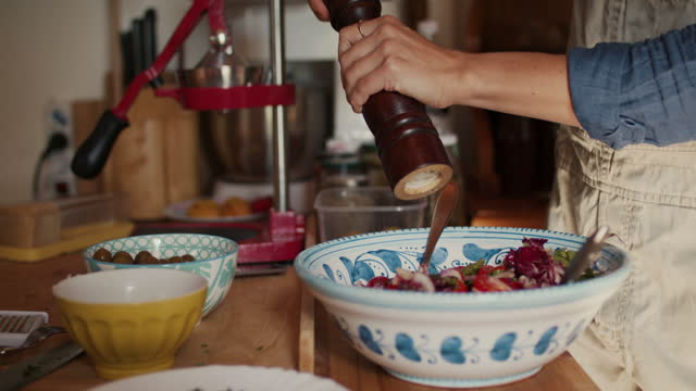 woman mixing salad putting pepper on - spice stock videos & royalty-free footage