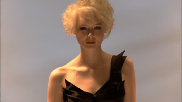 cu ms woman modeling asymmetrical black dress on catwalk / london, england, uk - glamour stock-videos und b-roll-filmmaterial