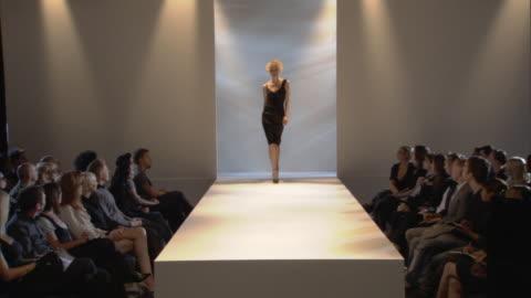 ws woman modeling asymmetrical black dress on catwalk while audience watches / london, england, uk - sfilata di moda video stock e b–roll