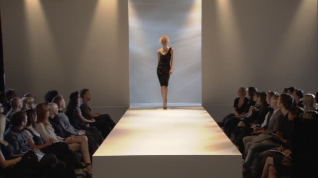 vidéos et rushes de ws woman modeling asymmetrical black dress on catwalk while audience watches / london, england, uk - fashion show