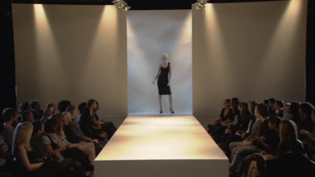 WS Woman modeling asymmetrical black dress on catwalk while audience watches / London, England, UK