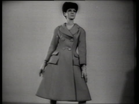 B/W woman modeling coat in designer showroom / SOUND