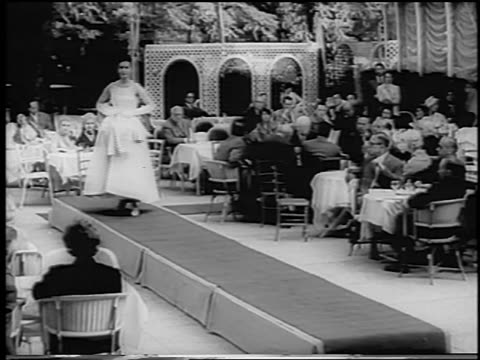 B/W 1960 woman modeling evening dress removing outer skirt on runway / Paris / newsreel