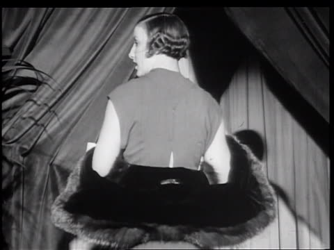 B/W 1934 woman modeling fur coat turning in front of curtain / New York City