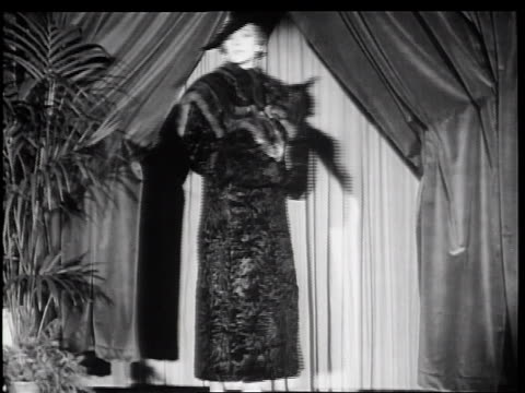 b/w 1934 woman modeling fur coat turning + walking off of fashion runway / new york city - カーテン止め点の映像素材/bロール