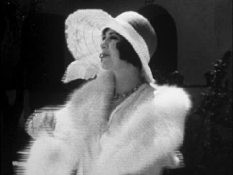 b/w 1929 woman modeling fur stole + large wide-brimmed white hat outdoors / newsreel - cappotto invernale video stock e b–roll