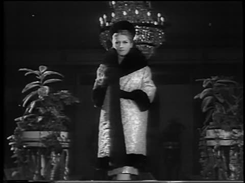 woman modeling fur-lined coat opening coat to reveal evening dress / rome / newsreel - 毛皮のコート点の映像素材/bロール