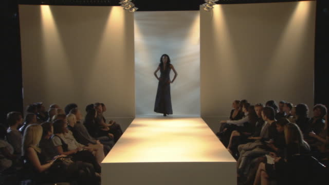 WS Woman modeling long halter dress on catwalk while audience watches / London, England, UK