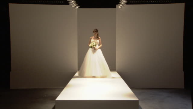 ws woman modeling wedding dress and holding bouquet of flowers on catwalk / london, england, uk - この撮影のクリップをもっと見る 1064点の映像素材/bロール