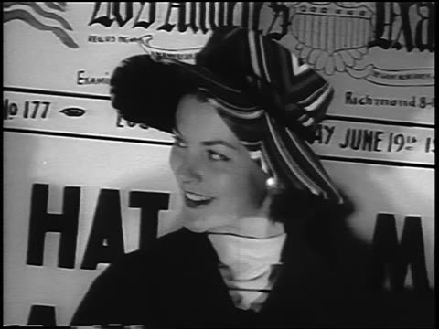 b/w 1956 woman modelling hat in front of large newspaper headline / newsreel - haute couture stock videos and b-roll footage