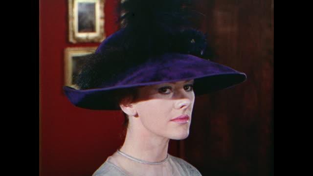 vidéos et rushes de montage woman models a large hat with flowers and feathers in an art gallery / uk - chapeau