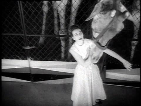 vidéos et rushes de 1954 montage woman models a long dress designed for tall women while a giraffe looks on - 1954