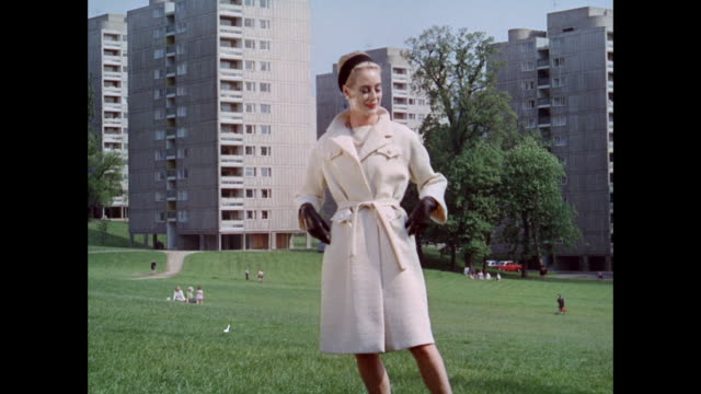MS Woman models belted overcoat at modern residential buildings / UK
