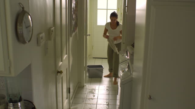 WS, PAN, Woman mopping tile floor in laundry room, Hollywood, California, USA