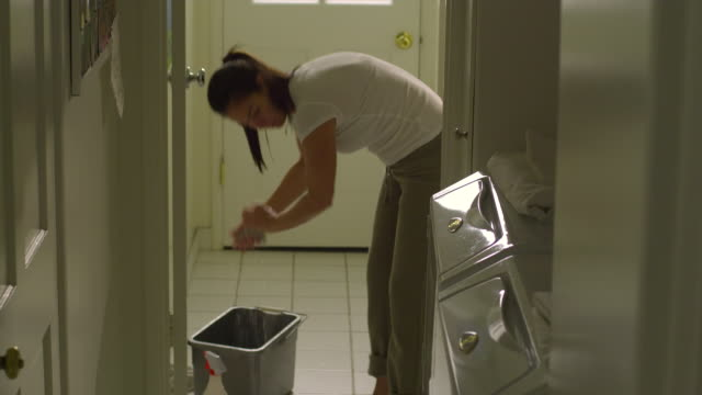 MS, TU, Woman mopping tile floor in laundry room, Hollywood, California, USA