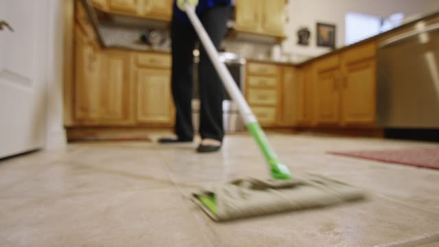 a woman mops the floor of a residential kitchen - lavori di casa video stock e b–roll