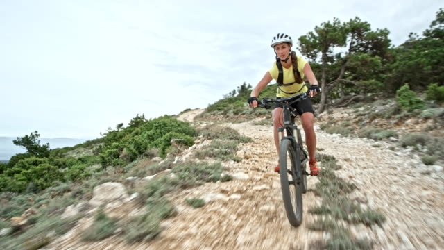 Woman mountain biking down a gravel road
