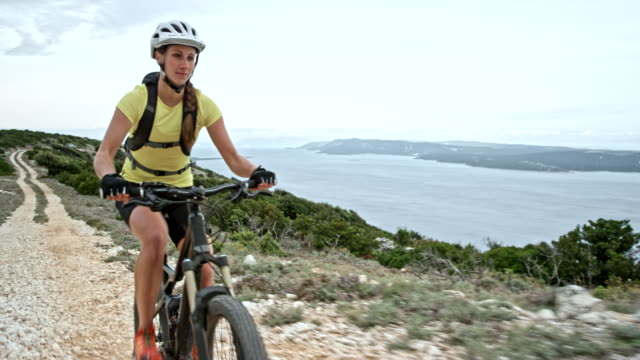 woman mountain biking on a mountain above a coastline - motorcycle biker stock videos & royalty-free footage