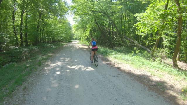 MS Woman ciclismo de montaña en camino de ripio en el bosque soleado