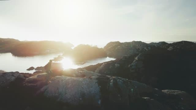 stockvideo's en b-roll-footage met bergwandelen van de vrouw door een fjord in noorwegen - richel