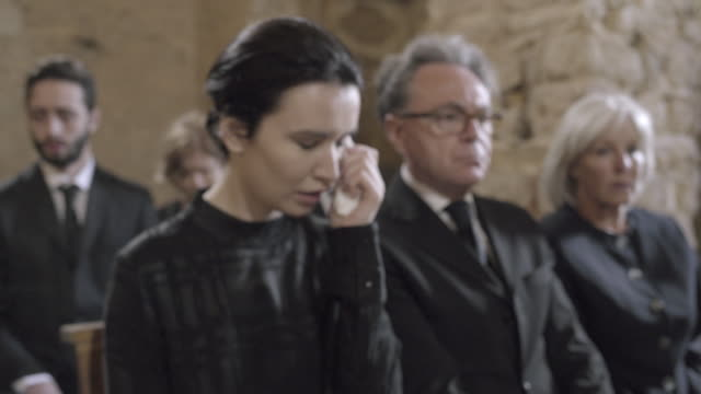 Woman mourning at funeral service in church