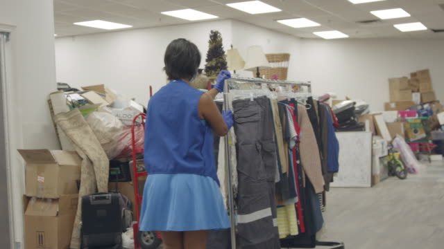 woman moves clothing rack - fatcamera stock videos & royalty-free footage